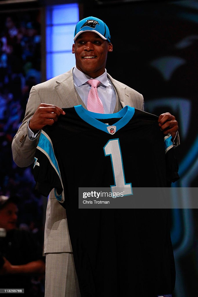 Cam Newton, #1 overall pick by the Carolina Panthers holds up a jersey on stage after he was picked during the 2011 NFL Draft at Radio City Music Hall on April 28, 2011 in New York City.