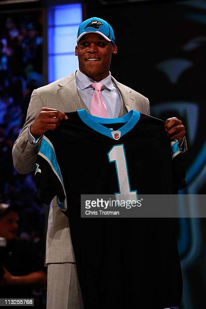 Cam Newton, #1 overall pick by the Carolina Panthers holds up a jersey on stage after he was picked during the 2011 NFL Draft at Radio City Music...