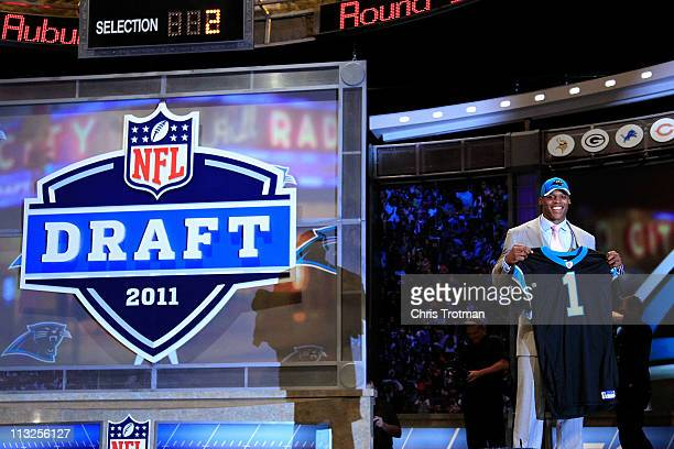 Cam Newton #1 overall pick by the Carolina Panthers holds up a jersey on stage after he was picked during the 2011 NFL Draft at Radio City Music Hall...