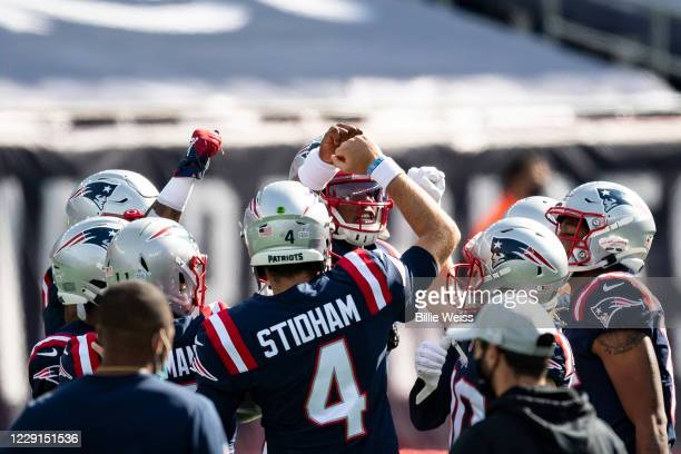 Cam Newton and Jarrett Stidham of the New England Patriots huddle with teammates before a game against the Denver Broncos at Gillette Stadium on...
