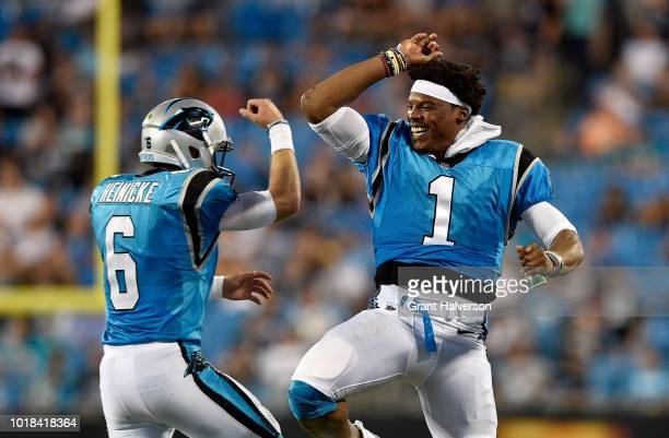 Cam Newton and teammate Taylor Heinicke of the Carolina Panthers react after a third quarter touchdown against the Miami Dolphins during the game at...