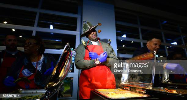 Cam Newton center strikes a pose inbetween serving macaroni and cheese to children during his 'Cam's Thanksgiving Jam' event on Monday Nov 20 in...