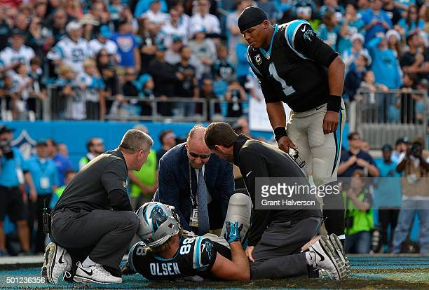 Cam Newton checks on Greg Olsen of the Carolina Panthers after Olsen was injured at the end of the first half during their game against the Atlanta...