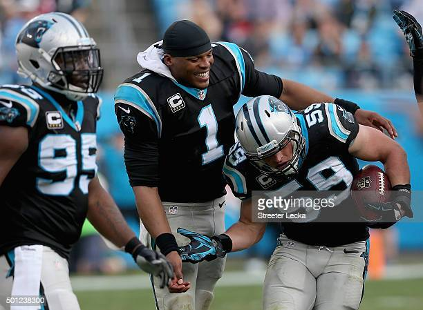 Cam Newton congratulates teammate Luke Kuechly of the Carolina Panthers after Kuechly made an interception in the third quarter during their game...
