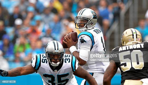 Cam Newton drops back to pass as Mike Tolbert of the Carolina Panthers defends against Stephone Anthony of the New Orleans Saints in the first...