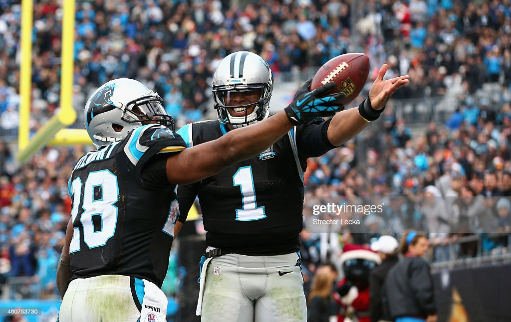 Cam Newton #1 helps Jonathan Stewart #28 of the Carolina Panthers celebrate his 4th quarter touchdown against the Cleveland Browns during their game at Bank of America Stadium on December 21, 2014 in Charlotte, North Carolina.