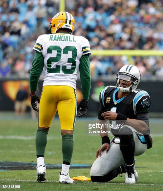 Cam Newton of the Carolina Panthers and Damarious Randall of the Green Bay Packers watch a replay in the third quarter during their game at Bank of...