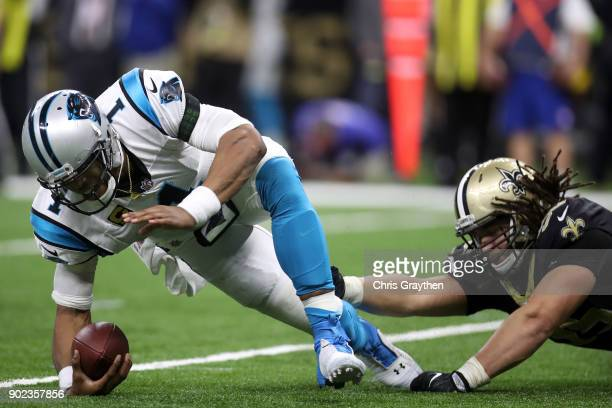 Cam Newton of the Carolina Panthers avoids a tackle by Tyeler Davison of the New Orleans Saints at the MercedesBenz Superdome on January 7 2018 in...