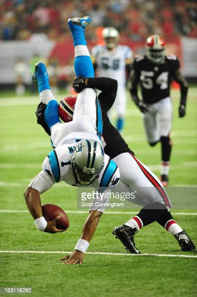 Cam Newton of the Carolina Panthers carries the ball for a first down against Robert McClain of the Atlanta Falcons at the Georgia Dome on September...