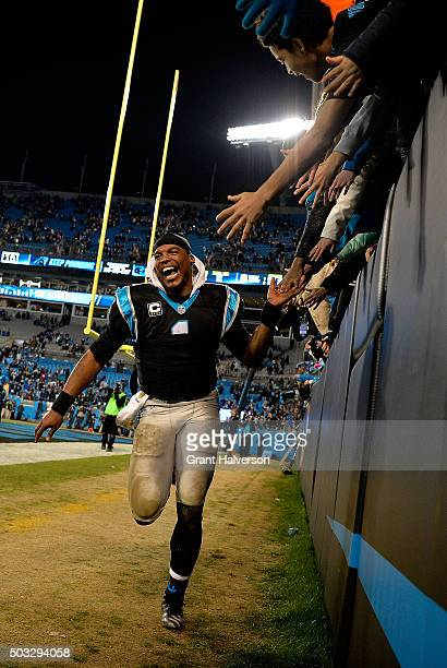 Cam Newton of the Carolina Panthers celebrates with fans after a win against the Tampa Bay Buccaneers at Bank of America Stadium on January 3 2016 in...