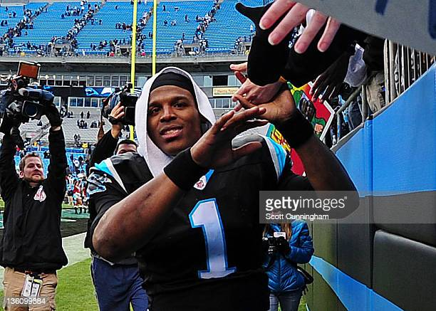 Cam Newton of the Carolina Panthers celebrates with fans after the game against the Tampa Bay Buccaneers at Bank of America Stadium on December 24,...