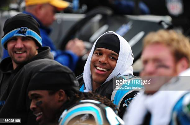 Cam Newton of the Carolina Panthers celebrates with teammates after setting the NFL record for passing yards as a rookie during the game against the...