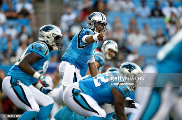 Cam Newton of the Carolina Panthers checks down the line against the Miami Dolphins in the first quarter during the game at Bank of America Stadium...