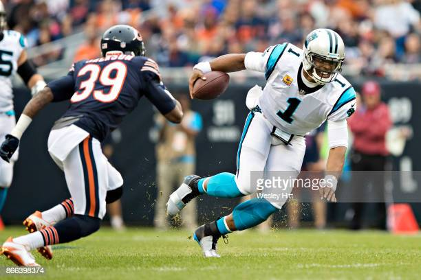 Cam Newton of the Carolina Panthers dives for a first down to avoid the tackle of Eddie Jackson of the Chicago Bears at Soldier Field on October 22...