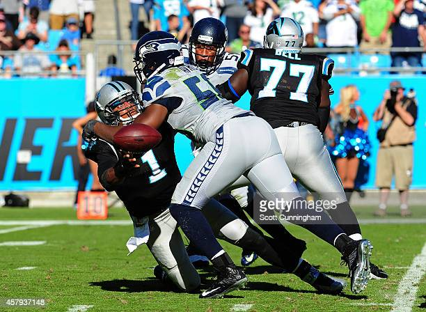 Cam Newton of the Carolina Panthers flips the ball away as he is pressured by Cliff Avril of the Seattle Seahawks on October 26 2014 at Bank of...