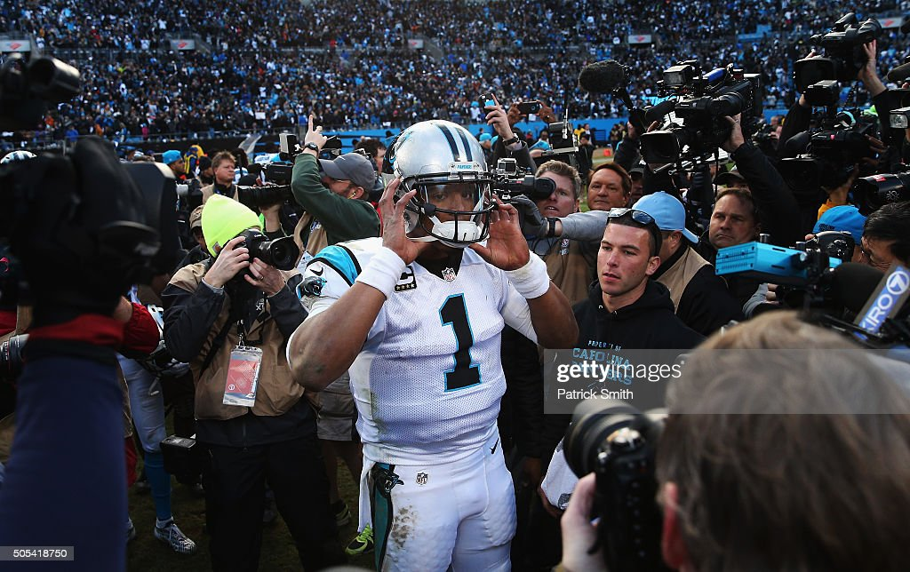 Cam Newton #1 of the Carolina Panthers gets swarmed by the media after their 31-24 victory over the Seattle Seahawks at the NFC Divisional Playoff Game at Bank of America Stadium on January 17, 2016 in Charlotte, North Carolina.