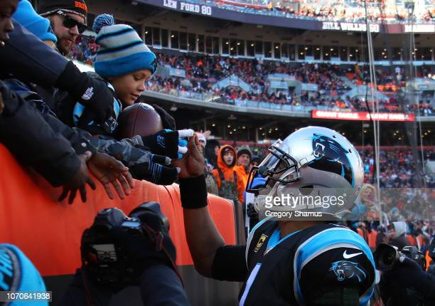 Cam Newton of the Carolina Panthers gives a ball to a fan after a touchdown by Christian McCaffrey during the second quarter against the Cleveland...