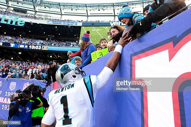 Cam Newton of the Carolina Panthers gives a touchdown ball to a young fan in the stands in the third quarter against the New York Giants during their...