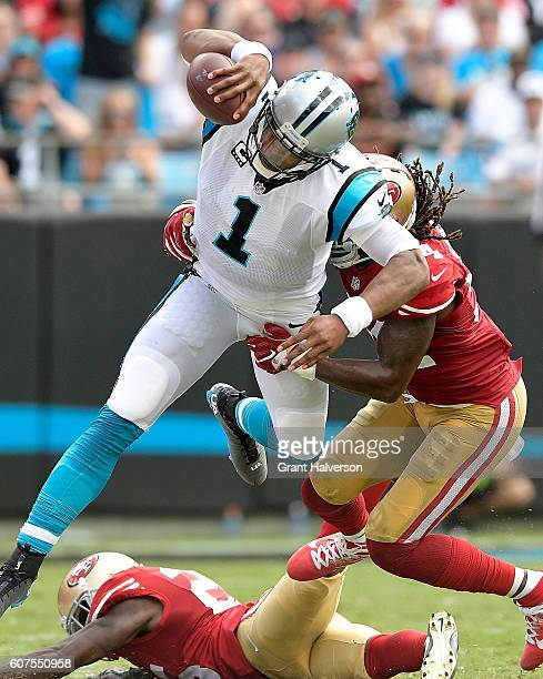 Cam Newton of the Carolina Panthers hurdles Ray-Ray Armstrong and Jimmie Ward of the San Francisco 49ers during the game at Bank of America Stadium...