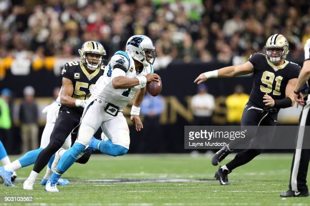 Cam Newton of the Carolina Panthers is chased by Craig Robertson and Trey Hendrickson of the New Orleans Saints during the first half of the NFC Wild...