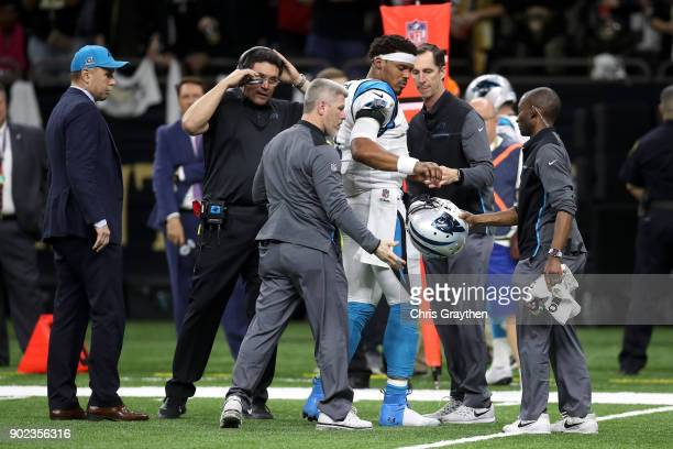 Cam Newton of the Carolina Panthers is checked on the sideline after a tackle during the game against the New Orleans Saints at the MercedesBenz...