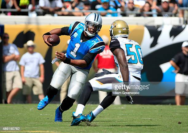 Cam Newton of the Carolina Panthers is defended by Telvin Smith of the Jacksonville Jaguars during the game at EverBank Field on September 13 2015 in...