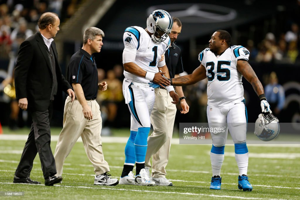 Cam Newton #1 of the Carolina Panthers is helped off the field after being hurt during a game against the New Orleans Saints at Mercedes-Benz Superdome on December 30, 2012 in New Orleans, Louisiana. The Panthers defeated the Saints 44-38.