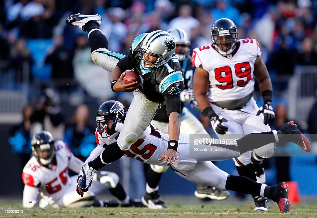Cam Newton #1 of the Carolina Panthers is tackled by William Moore #24 of the Atlanta Falcons during their game at Bank of America Stadium on December 11, 2011 in Charlotte, North Carolina.