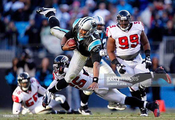 Cam Newton of the Carolina Panthers is tackled by William Moore of the Atlanta Falcons during their game at Bank of America Stadium on December 11,...