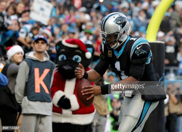 Cam Newton of the Carolina Panthers lights an imaginary birthday candle on the ball before giving it to a fan after scoring the game winning...