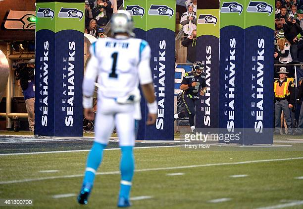 Cam Newton of the Carolina Panthers looks on as Russell Wilson of the Seattle Seahawks takes the field prior to the 2015 NFC Divisional Playoff game...