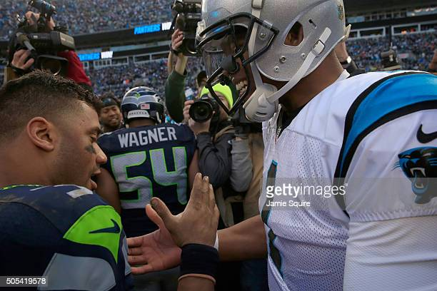 Cam Newton of the Carolina Panthers meets Russell Wilson of the Seattle Seahawks on the field after the NFC Divisional Playoff Game at Bank of...