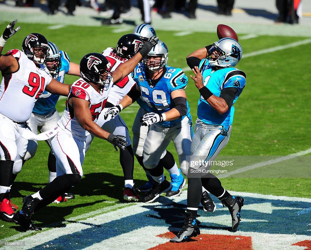 Cam Newton #1 of the Carolina Panthers passes despite pressure from Osi Umenyiora #50 of the Atlanta Falcons at Bank of America Stadium on November 3, 2013 in Charlotte, North Carolina