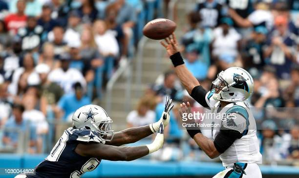 Cam Newton of the Carolina Panthers passes over Demarcus Lawrence of the Dallas Cowboys in the third quarter during their game at Bank of America...