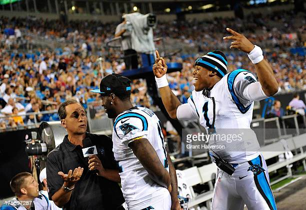 Cam Newton of the Carolina Panthers photobombs a television interview with teammate Brandon LaFell during a preseason win over the Chicago Bears at...