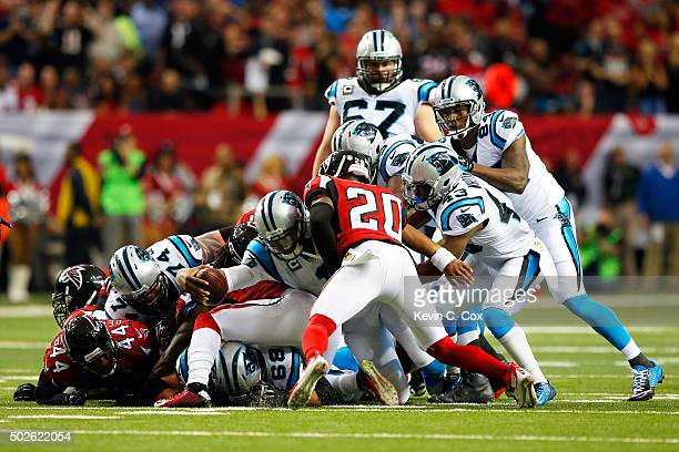 Cam Newton of the Carolina Panthers pulls the pile and reaches for a first down during the first half against the Atlanta Falcons at the Georgia Dome...