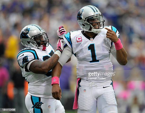 Cam Newton of the Carolina Panthers reacts to Sharrif Floyd of the Minnesota Vikings called on a face mask penalty as teammate Mike Tolbert adjusts...