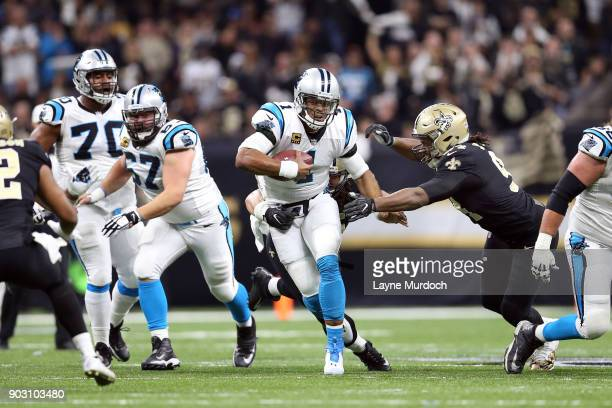 Cam Newton of the Carolina Panthers runs the ball against Cameron Jordan of the New Orleans Saints during the first half of the NFC Wild Card playoff...