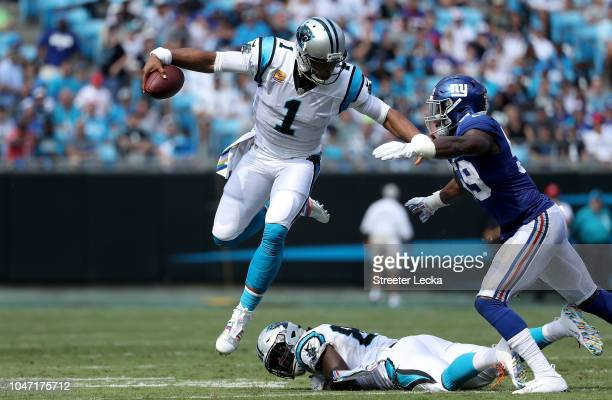 Cam Newton of the Carolina Panthers runs the ball against Lorenzo Carter of the New York Giants in the second quarter during their game at Bank of...