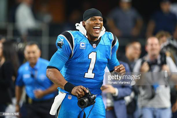 Cam Newton of the Carolina Panthers runs with a camera after a 3314 win against the Dallas Cowboys at ATT Stadium on November 26 2015 in Arlington...