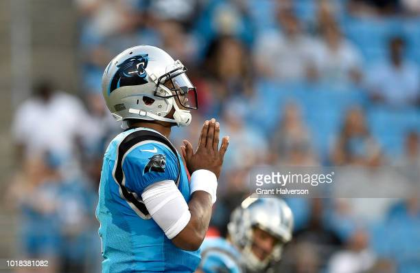 Cam Newton of the Carolina Panthers says a prayer at the line before the first play against the Miami Dolphins at Bank of America Stadium on August...