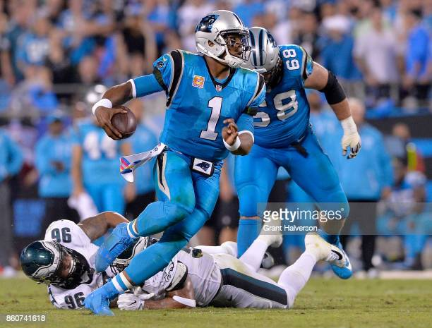 Cam Newton of the Carolina Panthers scrambles away from Derek Barnett of the Philadelphia Eagles during their game at Bank of America Stadium on...