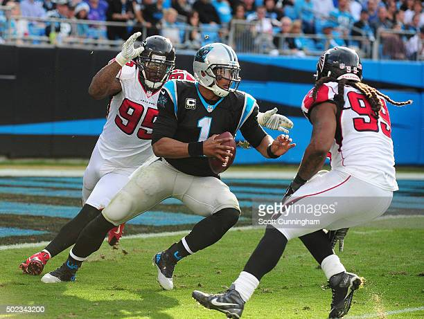 Cam Newton of the Carolina Panthers scrambles away from Jonathan Babineaux and Adrian Clayborn of the Atlanta Falcons at Bank Of America Stadium on...