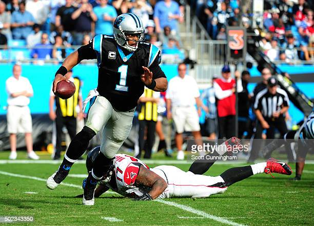 Cam Newton of the Carolina Panthers scrambles away from Ra'Shede Hageman of the Atlanta Falcons at Bank Of America Stadium on December 13 2015 in...