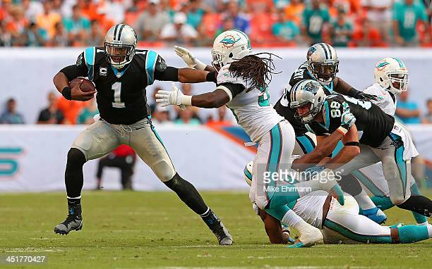 Cam Newton of the Carolina Panthers scrambles during a game against the Miami Dolphins at Sun Life Stadium on November 24 2013 in Miami Gardens...