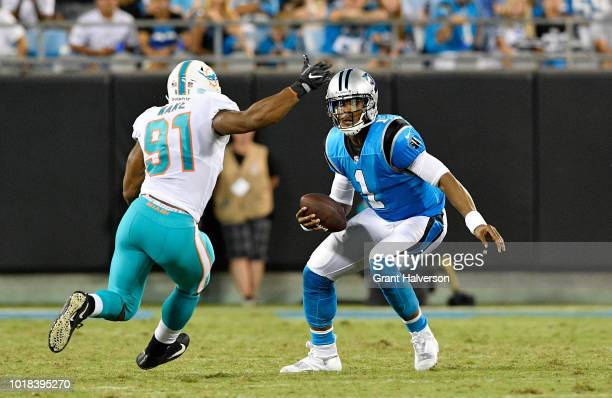 Cam Newton of the Carolina Panthers scrambles from Cameron Wake of the Miami Dolphins in the second quarter during the game at Bank of America...