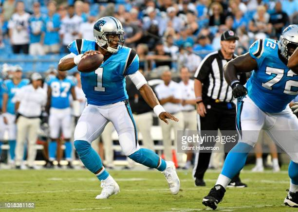Cam Newton of the Carolina Panthers scrambles from the Miami Dolphins defense in the first quarter during the game at Bank of America Stadium on...