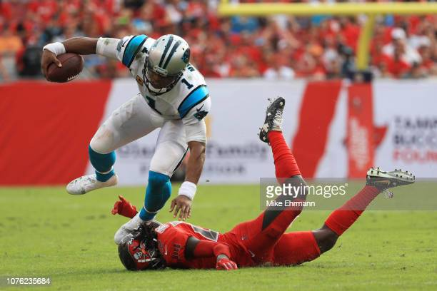 Cam Newton of the Carolina Panthers trips over De'Vante Harris of the Tampa Bay Buccaneers in the fourth quarter at Raymond James Stadium on December...