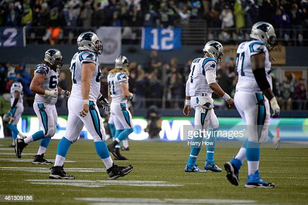 Cam Newton of the Carolina Panthers walks off the field after throwing an interception to Kam Chancellor of the Seattle Seahawks scoring a 90 yard...