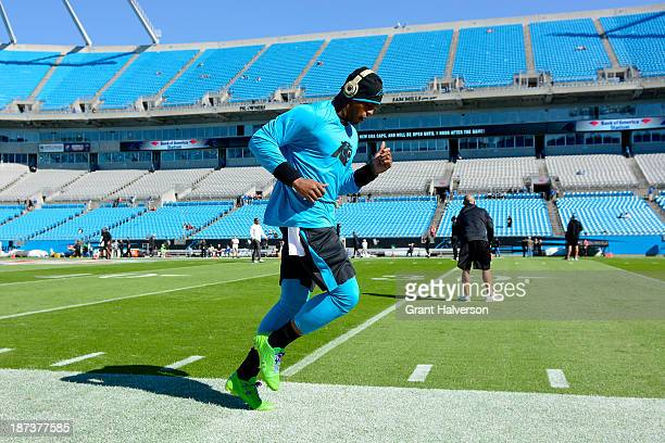 Cam Newton of the Carolina Panthers wears green Under Armour cleats as he warms up before a game against the Atlanta Falcons at Bank of America...